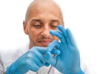 Adult Male Doctor In Blue Rubber Gloves Demonstrating Simulated Sexual Intercourse Or Penetration, Sex Education Concept