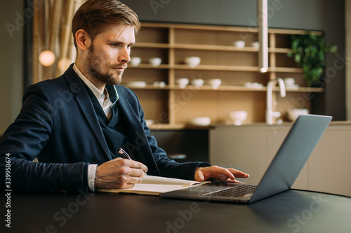 Confident businessman working remotely from a home kitchen with a laptop and notebook Fototapete