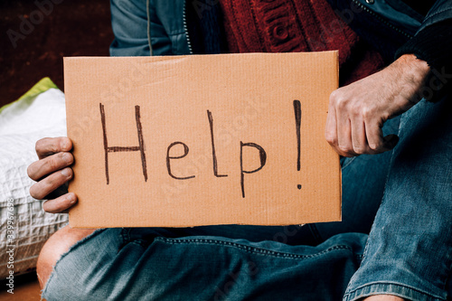 Fototapeta A homeless person holds a sign , asks for work, and seeks help