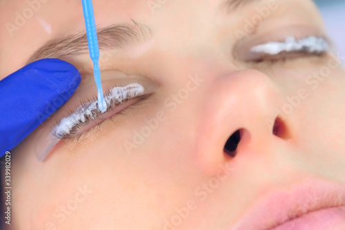 Fototapeta Beautician applying solution for lamination on woman lashes on curlers, lift eyelashes procedure in beauty salon, face closeup