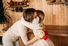 Mom And Daughter Hugging In Masks. Family Quarantined. Mother's Day At Home.