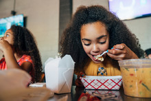 Girl Eating Take Out Food With Chopsticks