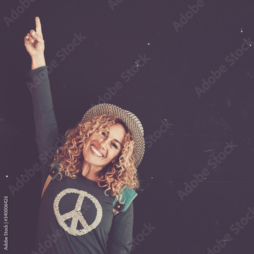 Cheerful beautiful caucasian adult woman with blonde curly hair and trendy hat sign with finger and smile at the camera for sale or offer message - black wall in background and peace on the shirt Fototapete