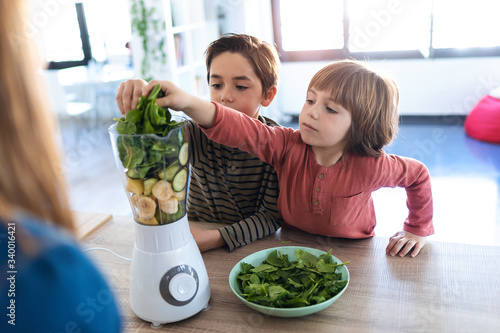 Fotografia Two boys helping his mother to prepare a detox juice with blender in the kitchen at home