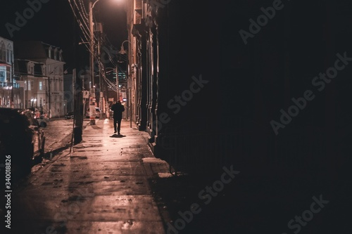 shadowy figure walking down street at night