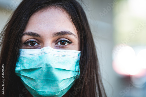Photo Close up portrait of Latino young woman wearing a protective surgical face mask