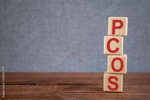 Abbreviation PCOS (polycystic ovarian syndrome) text acronym on wooden cubes on dark wooden backround Canvas Print