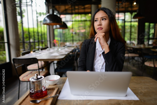 Foto Young beautiful Asian businesswoman thinking while using laptop