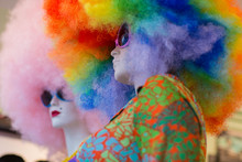 Two White Mannequins Wearing Sunglasses With Very Big Curly Colorful Wigs On Their Head, One Pink And The Other Rainbow Style