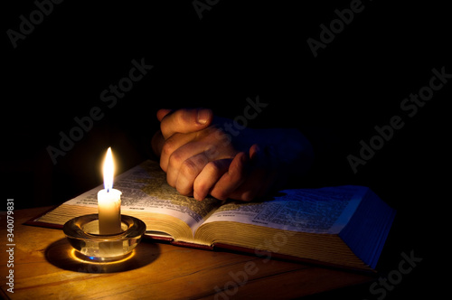 Photo Hands folded in prayer over Scriptures