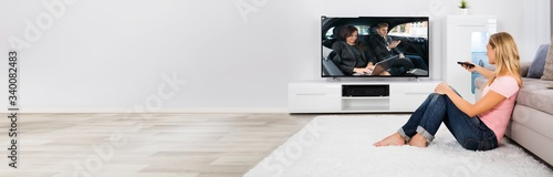 Fotografie, Tablou Woman Sitting On Carpet Watching Television
