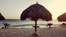 Thatched Roof Parasols At Beach During Sunset