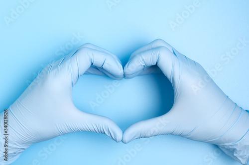 Obraz na plátně blue hand gloves making heart shape on blue background for care, love or support