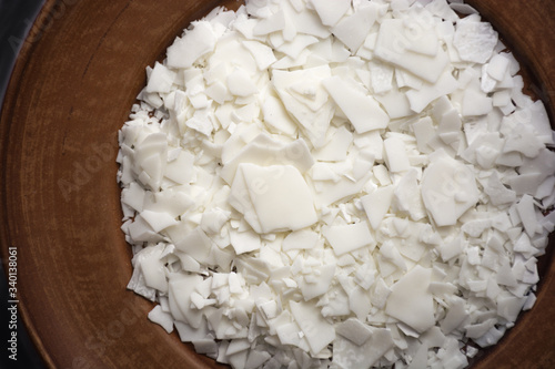 Tablou Canvas Close up of white soy wax flakes for candle making on brown plate