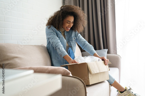 Fényképezés Excited african young woman shopper opening parcel box at home