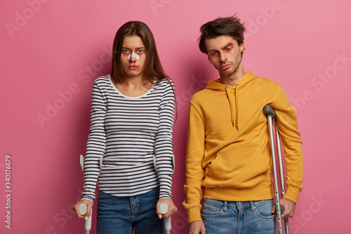 фотографія Photo of woman and man got into accident during reckless motorbike driving, pose on crutches with sad faces, have many bruises and abrasion