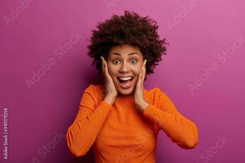 Obraz na plátně Happy energetic woman grabs face, hears wonderful news, realises she won huge mo