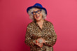 Horizontal shot of happy elderly woman happy to meet old friend, remembers her youth, wears elegant leopard dress and hat, being on pension, isolated over pink background. People and age concept