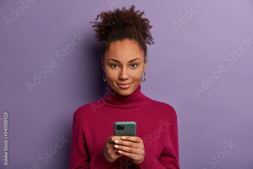Fotografering Photo of pleased dark skinned millennial girl holds mobile phone, waits for call
