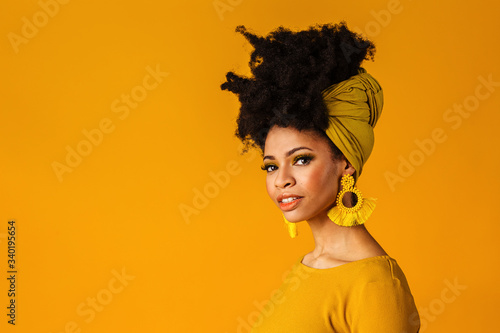 Portrait of a serious young woman with big yellow tassel beaded earrings and afr Canvas Print