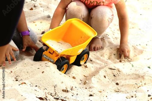 Stampa su Tela Children With Toy Wheelbarrow Playing On Sand