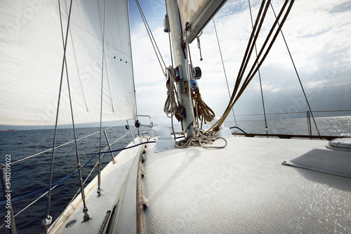 Fototapeta White yacht sailing on a sunny summer day. Close-up view from the deck to the bow, mast and sails. Waves and water splashes. Clear blue sky. Gulf of Finland obraz na płótnie