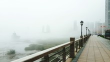 Railing On Bridge Over River Against Sky In Foggy Weather