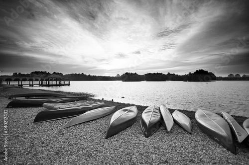 Valokuvatapetti Upside Down Canoes At Lakeshore Against Cloudy Sky