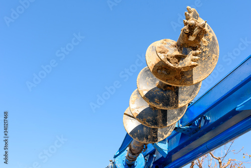 Fototapeta Tracer tractor with auger for soil drilling for piles installation