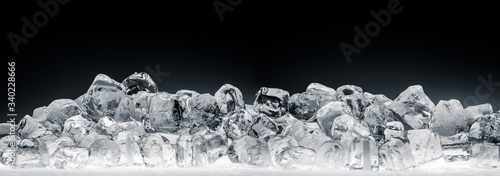 Heap of translucent crushed ice cubes on black background. Wide format.