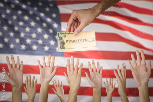 Foto Man handing Stimulus check to people with the USA flag on the Background