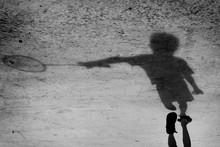 Shadow Of Boy Holding Badminton Racket