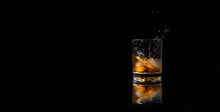 Glass Of Whiskey With Ice And A Splash On A Black Background
