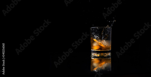Fényképezés glass of whiskey with ice and a splash on a black background