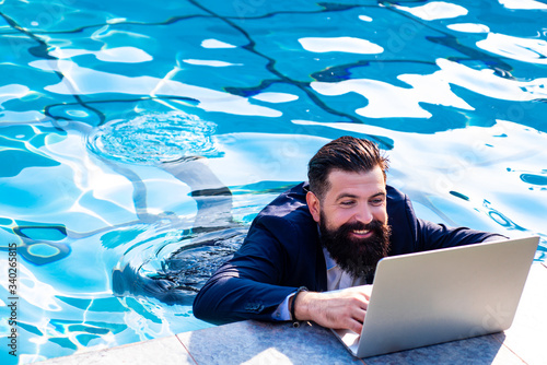 Obraz Business man in suit with laptop on swimming pool. Funny businessman relaxing with laptop. - fototapety do salonu