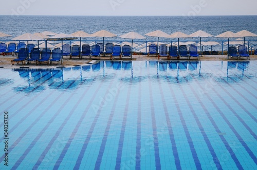 Fotografia Lounge Chairs At Poolside At Beach Against Sky