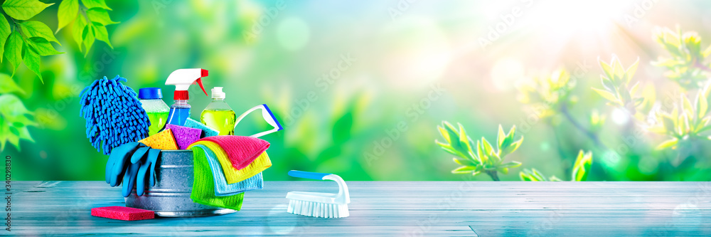 Fototapeta Bucket Of Cleaning Supplies On Wooden Table With Fresh Spring Background - Cleaning Services Concept