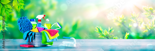 Fototapeta Bucket Of Cleaning Supplies On Wooden Table With Fresh Spring Background - Cleaning Services Concept obraz