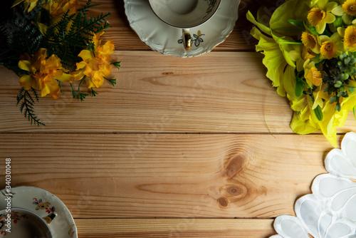 kompozycja filiżanki i kwiatów ma tle stołu sosnowego.