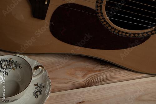 Kompozycja filiżanki i gitary na tle stołu z sosny.