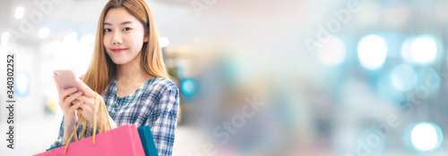 Papel de parede Smiling young Asian woman with shopping colour bags over mall background