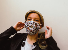 Young Blonde Caucasian Woman Wearing Colorful Face Mask Made Of Fabric Isolated Infront Of White Background