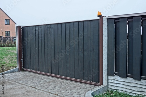 Obraz gray black private gate and wooden plank fence on a rural street - fototapety do salonu