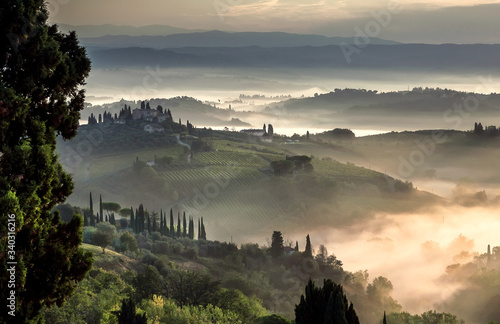 Beautiful sunrise over misty landscape of Italy. Early morning over rural area with gardens, farms, trees, fields in Tuscany province