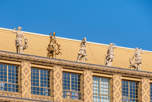 Golden Statue Besides Marble Statues On Top Of Yellow Brick Facade With Pattern And Big Windows