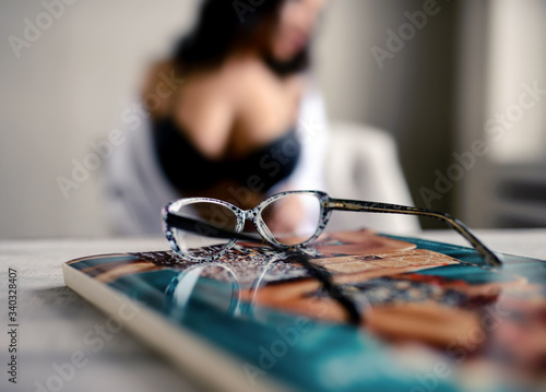 Fotografía Glasses on the table and girl out of focus, vision correction