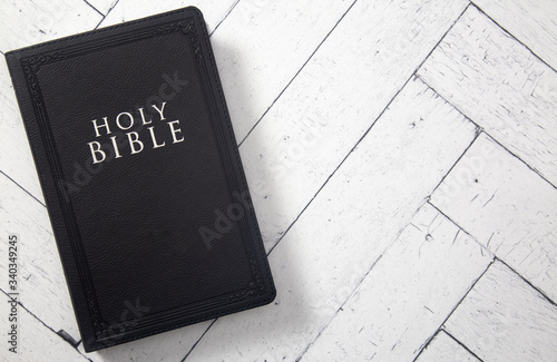 Canvastavla A Black Holy BIble on a White Wooden Table