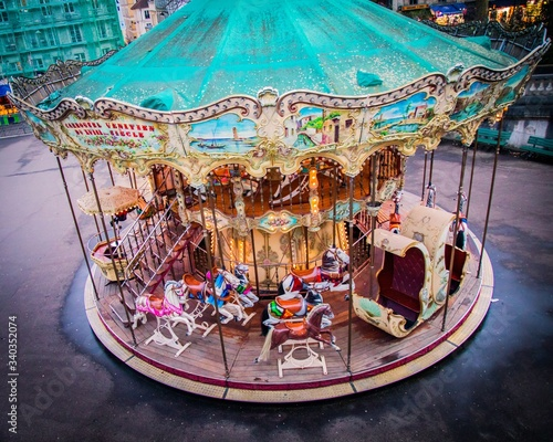 Fototapeta High angle shot of a carousel surrounded by buildings and lights in Montmartre i