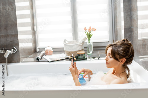 Photographie Young woman taking a bath, lying with a smart phone in bathtub with foam and rub