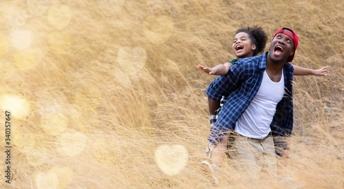 beautiful happy african american father and daughter happy and smiling on hay or dry grass Fototapeta